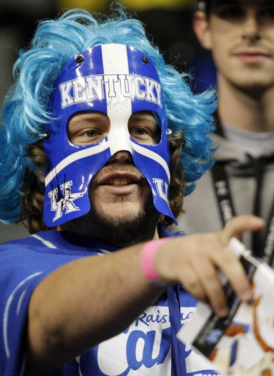 FILE - In this Nov. 19, 2013 file photo, Kentucky fan and student David Green gestures before an NCAA college basketball game between Kentucky and Texas-Arlington, in Lexington, Ky. Rivals Louisville and Kentucky will meet Friday, March 28, 2014, in Indianapolis, which will be invaded by a sea of fans clad in blue and red gear fans with the game just three hours away from both schools.(AP Photo/James Crisp, File)