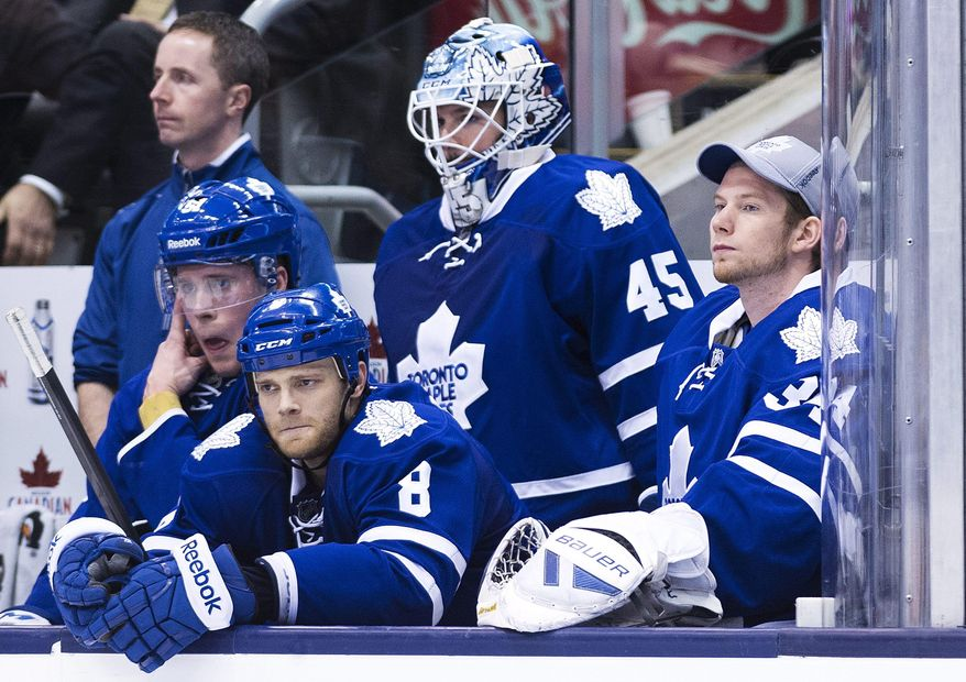 Toronto Maple Leafs goalie Jonathan Bernier (45) and James Reimer, right, watch from the bench with  Jake Gardiner, left, and Tim Gleason (8) after Bernier was pulled in the last minutes of the game against the St. Louis Blues during third period NHL hockey action in Toronto on Tuesday, March 25, 2014. (AP Photo/The Canadian Press, Nathan Denette)