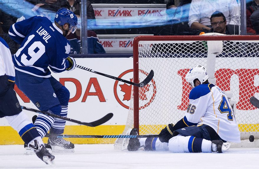 Toronto Maple Leafs forward Joffrey Lupul (19) scores as St. Louis Blues defenseman Roman Polack (46) tries to turn the puck away during the first period of an NHL hockey game Tuesday, March 25, 2014, in Toronto. (AP Photo/The Canadian Press, Nathan Denette)