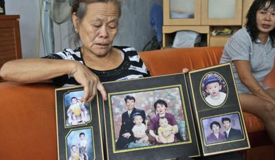 """Suwarni the mother of Sugianto Lo, who was onboard the Malaysia Airlines plane MH370 with his wife Vinny, shows her son's family portraits at her residence in Medan, North Sumatra, Indonesia, Tuesday, March 25, 2014. After 17 days of desperation and doubt over the missing Malaysia Airlines jet, the country's officials said an analysis of satellite data points to a """"heartbreaking"""" conclusion: Flight 370 met its end in the southern reaches of the Indian Ocean, and none of those aboard survived. (AP Photo/Binsar Bakkara)"""
