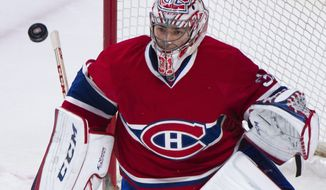 Montreal Canadiens goaltender Carey Price watches the puck during the first period of an NHL hockey game against the Buffalo Sabres, Tuesday, March 25, 2014, in Montreal. (AP Photo/The Canadian Press, Graham Hughes)