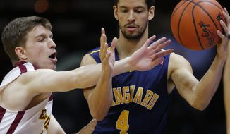 Emmanuel guard Luke Miller, left, reaches in on Vanguard guard Preston Wynne (4) during the first half of an NAIA college basketball game and finals of the men's national championship tournament in Kansas City, Mo., Tuesday, March 25, 2014. (AP Photo/Orlin Wagner)
