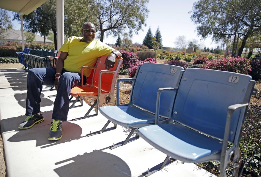 In this March 13, 2014 photo, Dusty Baker sits in a row of old seats from stadiums at all of his stops as a player by a batting cage at his home in Granite Bay, Calif. They're Nos. 11 and 12, since Baker wore 12 on his jersey. Out of uniform for the first time since taking 2007 off between managerial jobs with the Cubs and Reds, Baker is not slowing down much from his pressure-packed days in the dugout. (AP Photo/Eric Risberg)