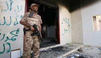FILE - This Sept, 14, 2012 file photo shows a Libyan military guard standing in front of one of the U.S. Consulate's burnt out buildings during the visit of  President Mohammed el-Megarif, to the U.S. Consulate to express sympathy for the death of the American ambassador, Chris Stevens and his colleagues in the deadly attack on the Consulate. The Pentagon says Congress' multiple investigations of the deadly 2012 attack on the U.S. diplomatic mission in Benghazi, Libya, have cost the department millions of dollars and thousands of hours of personnel time. (AP Photo/Mohammad Hannon, File)