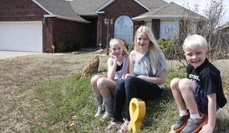 In this Monday, March 17, 2014 photo, Jennifer Hunt, center, poses for a photo outside her home with her son Trystan Morgan, 7, and daughter Silver Templeton, 11, in Noble, Okla. Hunt, whose husband was a soldier killed in the Fort Hood shooting, could get relief from a $6,000 tax bill under a measure Oklahoma legislators are considering that would grant some families benefits similar to those given after acts of terrorism. (AP Photo/Sue Ogrocki)