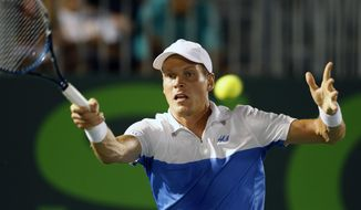 Tomas Berdych, of the Czech Republic, returns the ball to Joao Sousa, of Portugal, at the Sony Open Tennis tournament in Key Biscayne, Fla., Monday, March 24, 2014. (AP Photo/Joel Auerbach)