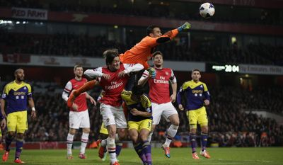 Swansea City's goalkeeper Michel Vorm punches the ball clear above Neil Taylor, 3, and Arsenal's Tomas Rosicky, center bottom left, during the English Premier League soccer match between Arsenal and Swansea City's at the Emirates Stadium in London, Tuesday, March 25, 2014. (AP Photo/Matt Dunham)