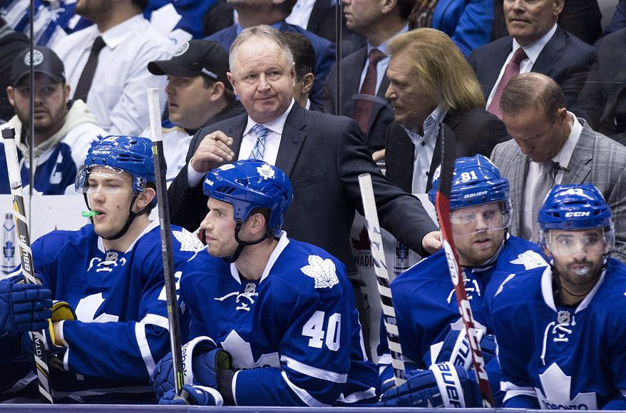 Toronto Maple Leafs head coach Randy Carlyle, back center, looks over his players while playing against the St. Louis Blues during second period NHL hockey action in Toronto on Tuesday, March 25, 2014. (AP Photo/The Canadian Press, Nathan Denette)