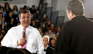 New Jersey Gov. Chris Christie, left, reacts to a question by John Dempsey, of Belmar, N.J., during a town hall meeting, Tuesday, March 25, 2014, in Belmar, N.J. Christie fielded questions from residents of the Jersey Shore community, which was hit hard by Super Storm Sandy in 2012, regarding issues concerning storm recovery and preparation. (AP Photo/Julio Cortez)