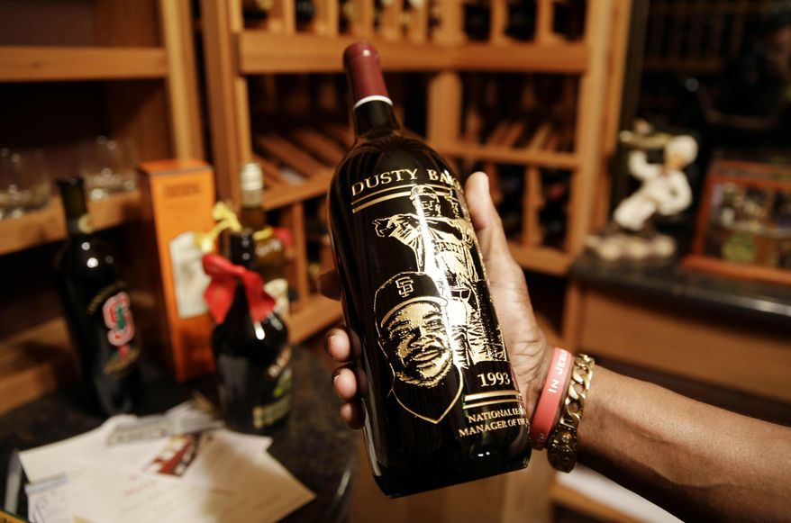 In this March 13, 2014 photo, Dusty Baker holds a specially etched bottle of wine given to him by Gary Matthews in the wine cellar of his home in Granite Bay, Calif. The bottle honors Baker being named the National League Manager of the Year in 1993. Out of uniform for the first time since taking 2007 off between managerial jobs with the Cubs and Reds, Baker is not slowing down much from his pressure-packed days in the dugout. (AP Photo/Eric Risberg)