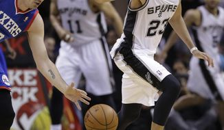 76ers' Byron Mullens, left, and San Antonio Spurs' Austin Daye (23) chase a loose ball during the second half of an NBA basketball game, Monday, March 24, 2014, in San Antonio. San Antonio won 113-91. (AP Photo/Eric Gay)