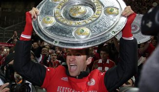 Bayern's Thomas Mueller lifts a mock champions trophy after the German Bundesliga soccer match between Hertha BSC Berlin and Bayern Munich in Berlin, Germany, Tuesday, March 25, 2014. (AP Photo/Michael Sohn)