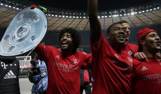 Bayern's Dante of Brazil, left, lifts a mock champions trophy as he and his teammates celebrate winning the German soccer championship after the German Bundesliga soccer match between Hertha BSC Berlin and Bayern Munich in Berlin, Germany, Tuesday, March 25, 2014. (AP Photo/Michael Sohn)