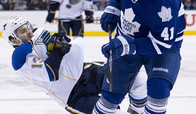Toronto Maple Leafs forward Nikolai Kulemin (41) takes out St. Louis Blues  Carlo Colaiacovo, left, during second period NHL hockey action in Toronto on Tuesday, March 25, 2014.  (AP Photo/The Canadian Press, Nathan Denette)