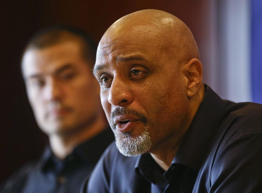 FILE - In this Dec. 3, 2013, file photo, Tony Clark, executive director of the Major League Baseball Players Association, answers questions during a news conference in San Diego. At rear is executive board member Jeremy Guthrie. People familiar with the negotiations tell The Associated Press that baseball players and management hope to reach a new drug agreement this week that would increase initial penalties for muscle-building steroids and decrease suspensions for some positive tests caused by unintentional use.  (AP Photo/Lenny Ignelzi, File)