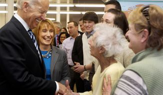 Vice President Joe Biden, accompanied by New Hampshire Gov. Maggie Hassan, shakes hands with Enis Sullivan, 101, of New Boston, N.H., during his visit to XMA Corporation, Tuesday, March 25, 2014 in Manchester, N.H.  Biden is making the rounds in this key political state critical to the Democrats' hopes of holding onto the Senate majority_and perhaps to Biden's own presidential ambitions in 2016. (AP Photo/Jim Cole)