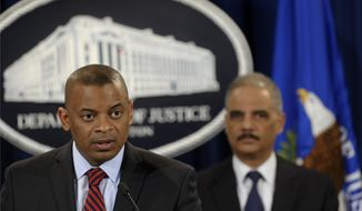 Transportation Secretary Anthony Foxx. left, accompanied by Attorney General Eric Holder, talks about a $1.2 billion settlement with Toyota over its disclosure of safety problems, Wednesday, March 19, 2014, during a news conference at the Justice Department in Washington.  (AP Photo/Susan Walsh)
