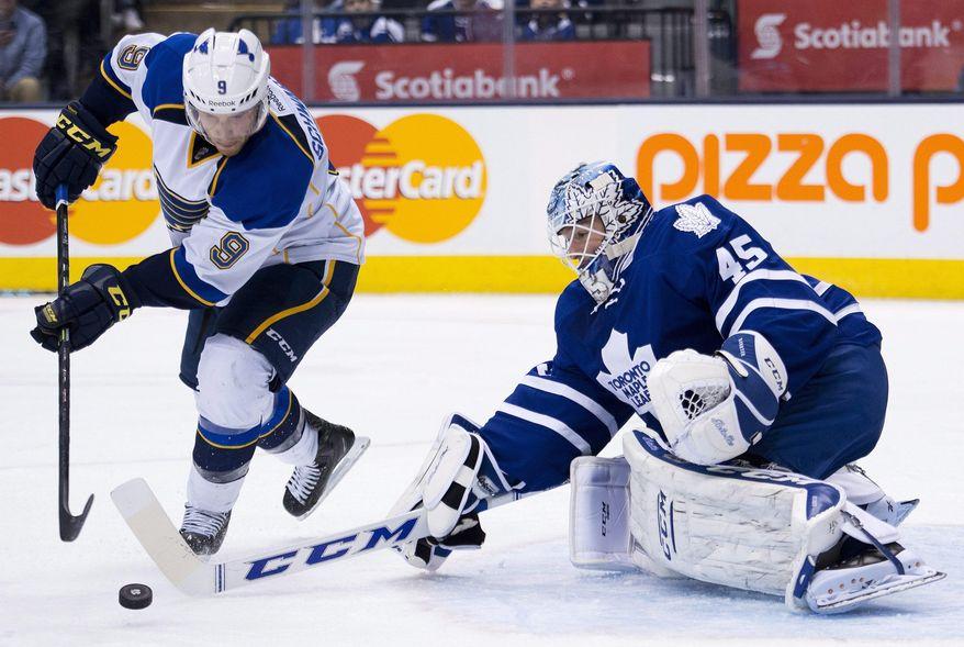 Toronto Maple Leafs goalie Jonathan Bernier poke checks St. Louis Blues forward Jaden Schwartz, left, during third period NHL hockey action in Toronto on Tuesday, March 25, 2014. (AP Photo/The Canadian Press, Nathan Denette)