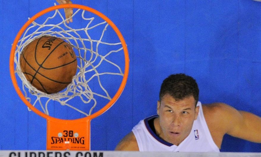 Los Angeles Clippers forward Blake Griffin watches his shot go in while laying on the floor during the first half of an NBA basketball game against the Milwaukee Bucks, Monday, March 24, 2014, in Los Angeles.  (AP Photo/Mark J. Terrill)