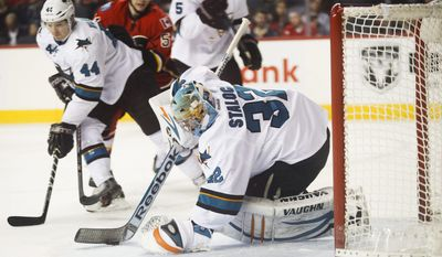 San Jose Sharks' goalie Alex Stalock, right, scoops up the puck as teammate Marc-Edouard Vlasic, left, keeps Calgary Flames' Kenny Agostino, center, away from the net during first period NHL hockey action in Calgary, Monday, March 24, 2014.(AP Photo/The Canadian Press, Jeff McIntosh)