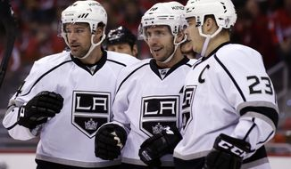 Los Angeles Kings right wing Justin Williams, left, center Mike Richards, right wing Dustin Brown  celebrate Richards' goal in the second period of an NHL hockey game against the Washington Capitals, Tuesday, March 25, 2014, in Washington. (AP Photo/Alex Brandon)