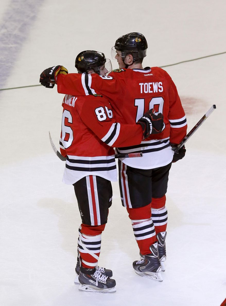 Chicago Blackhawks team captain, Jonathan Toews (19), puts his arm around rookie Teuvo Teravainen, after Teravainen's first NHL hockey game, against the Dallas Stars Tuesday, March 25, 2014, in Chicago. The Blackhawks won 4-2. (AP Photo/Charles Rex Arbogast)