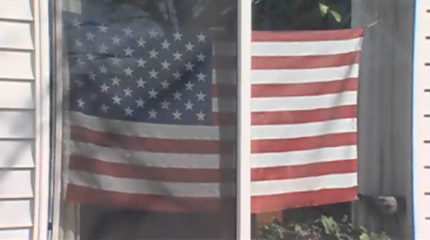 """An Oregon grandmother received a letter threatening her with eviction if she did not remove an American flag from her front window that the letter referred to as """"colored drapes."""" (KGW 8)"""
