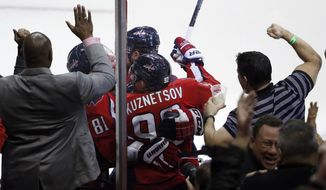 Washington Capitals center Evgeny Kuznetsov (92), from Russia, celebrates his goal to tie, with his teammates as the fans cheer, in the third period of an NHL hockey game against the Los Angeles Kings, Tuesday, March 25, 2014, in Washington. The Kings won 5-4 in a shootout. (AP Photo/Alex Brandon)