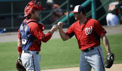 Washington Nationals pitcher Aaron Barrett, right, fist-bumps teammate Chris Snyder after closing out the ninth inning to end an exhibition spring training baseball game against the Miami Marlins, Saturday, March 15, 2014, in Jupiter, Fla. (AP Photo/David Goldman)