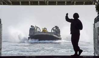 A Sailor directs Landing Craft Air Cushion (LCAC) 90, assigned to Assault Craft Unit (ACU) 5, as it enters the well deck of the amphibious transport dock ship USS Anchorage (LPD 23). (U.S. Navy)