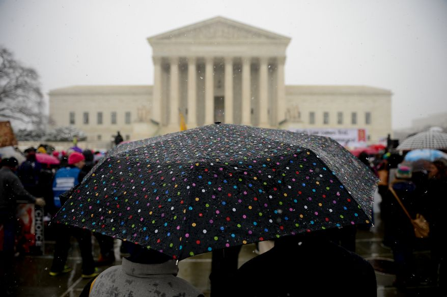Snow falls on rallys on both sides of the debate over private insurance plans must cover birth control at a rally outside the Supreme Court as the court hears oral arguments in Affordable Care Act challenges, the Sebelius v. Hobby Lobby Stores Inc. and Conestoga Wood Specialties Corp. v. Sebelius, Washington, D.C., Tuesday, March 25, 2014. (Andrew Harnik/The Washington Times)