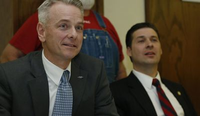 Army combat veteran and former Republican state Sen. Steve Russell, left, and former state Rep. Shane Jett, right, listen to a question during a candidate forum sponsored by the the Oklahoma Conservative Political Action Committee in Oklahoma City, Wednesday, March 26, 2014, as three of the Republican candidates vying for Oklahoma's open 5th Congressional District take part in the forum. (AP Photo/Sue Ogrocki)