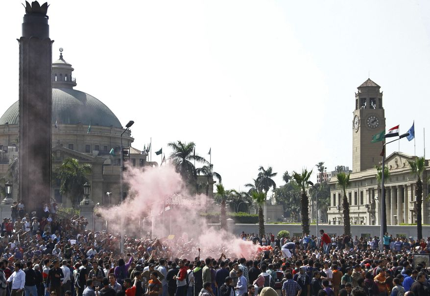A cloud of red smoke from flares fills the air as supporters of ousted President Mohammed Morsi chant slogans during a demonstration outside Cairo University in Giza, Egypt, Cairo's sister city, Wednesday, March 26, 2014. Clashes have erupted between security forces and students protests at a number of Egyptian universities against mass death sentences issued for hundreds of Islamists in a cursory trial. At Cairo University, hundreds of students who attempted to take their protest outside the campus Wednesday were met with volleys of tear gas from police. Khadiga el-Kholy, a student participating in the protest, said several students were injured. (AP Photo/Ahmed Abdel Fattah, El Shorouk) EGYPT OUT