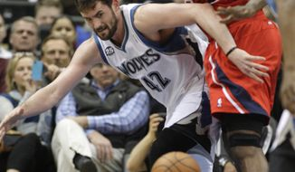 Minnesota Timberwolves forward Kevin Love (42) has the ball knocked away by Atlanta Hawks forward Elton Brand (42) during the first half of an NBA basketball game, Wednesday, March 26, 2014, in Minneapolis. (AP Photo/Paul Battaglia)