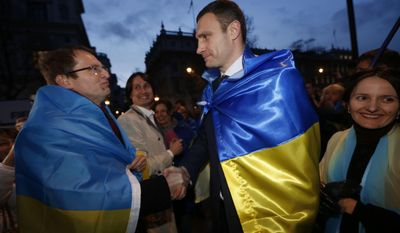 Ukraine's MP Vitali Klitschko, leader of the UDAR (Ukrainian Democratic Alliance for Reform) party, centre right, greets a protester outside 10 Downing Street in London after a meeting with British Prime Minister David Cameron and Foreign Secretary William Hague, Wednesday, March 26, 2014. (AP Photo/Sang Tan)