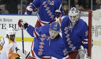 New York Rangers' Ryan McDonagh (27) blocks the goal as teammate Henrik Lundqvist (30) and Philadelphia Flyers' Wayne Simmonds (17) watch during the first period of an NHL hockey game Wednesday, March 26, 2014, in New York. (AP Photo/Frank Franklin II)
