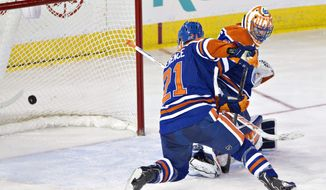 The San Jose Sharks score a goal on Edmonton Oilers goalie Ben Scrivens (30) as Andrew Ference (21) helps on defense during the second period of an NHL hockey game Tuesday, March 25, 2014, in Edmonton, Alberta. (AP Photo/The Canadian Press, Jason Franson)
