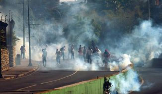 Demonstrators take cover form clouds of tear gas fired by the Bolivarian National Police during an anti-government protest in Caracas, Venezuela, Thursday, March 20, 2014. Thursday dawned with two more opposition politicians, San Cristobal Mayor Daniel Ceballos and San Diego Mayor Enzo Scarano, behind bars. Police used tear gas and water cannons to disperse a student-called protest of several thousand people in Caracas, some of those demonstrating against the arrests of the mayors. (AP Photo/Fernando Llano)