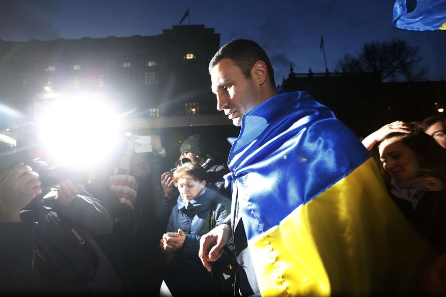Ukraine's MP Vitali Klitschko, leader of the UDAR (Ukrainian Democratic Alliance for Reform) party leaves, after talking to protesters after addressing them outside 10 Downing Street in London after a meeting with British Prime Minister David Cameron and Foreign Secretary William Hague, Wednesday, March 26, 2014. (AP Photo/Sang Tan)