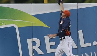 Houston Astros left fielder Robbie Grossman jumps but can not reach the two-run home run by New York Mets' Anthony Recker during the fifth inning of a spring exhibition baseball game in Kissimmee, Fla., Wednesday, March 26, 2014. (AP Photo/Carlos Osorio)