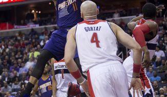 Phoenix Suns' Markieff Morris (11) dunks while Washington Wizards' Marcin Gortat (4) watches during the first half of an NBA basketball game in Washington, Wednesday, March 26, 2014. (AP Photo/Manuel Balce Ceneta)
