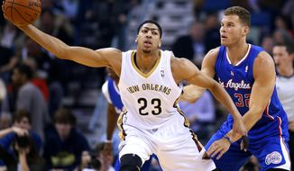 New Orleans Pelicans forward Anthony Davis (23) holds the ball as Los Angeles Clippers forward Blake Griffin (32) defends during the first half of an NBA basketball game in New Orleans, Wednesday, March 26, 2014. (AP Photo/Jonathan Bachman)