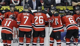 New Jersey Devils head coach Peter DeBoer, center left, talks strategy with his players during the third period of an NHL hockey game against the Toronto Maple Leafs Sunday, March 23, 2014, in Newark, N.J. The Devils won 3-2. (AP Photo/Mel Evans)