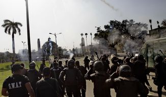 Riot police fire tear gas during clashes outside Cairo University in Giza, Egypt, Wednesday, March 26, 2014. Hundreds of largely Islamist university students in a number of universities protested Wednesday against the mass death sentences issued against more than 520 suspected supporters of President Mohammed Morsi in a cursory trial, setting off clashes that left dozens injured. At Cairo University, hundreds of students who attempted to take their protest outside the campus were met with volleys of tear gas from police. (AP Photo/Ahmed Abd El Latif, El Shorouk) EGYPT OUT