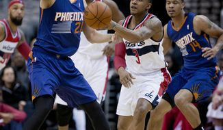 Washington Wizards Bradley Beal (3) passes the ball while Phoenix Suns' Alex Len (21) and Gerald Green (14) defend during the first half of an NBA basketball game in Washington, Wednesday, March 26, 2014. (AP Photo/Manuel Balce Ceneta)