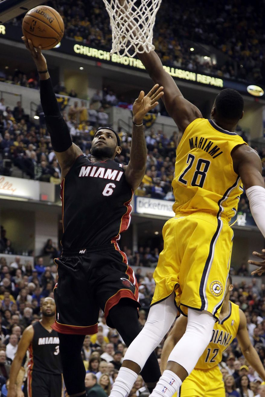 Miami Heat forward LeBron James (6) shoots around Indiana Pacers center Ian Mahinmi (28) during the first half of an NBA basketball game in Indianapolis, Wednesday, March 26, 2014. (AP Photo/AJ Mast)