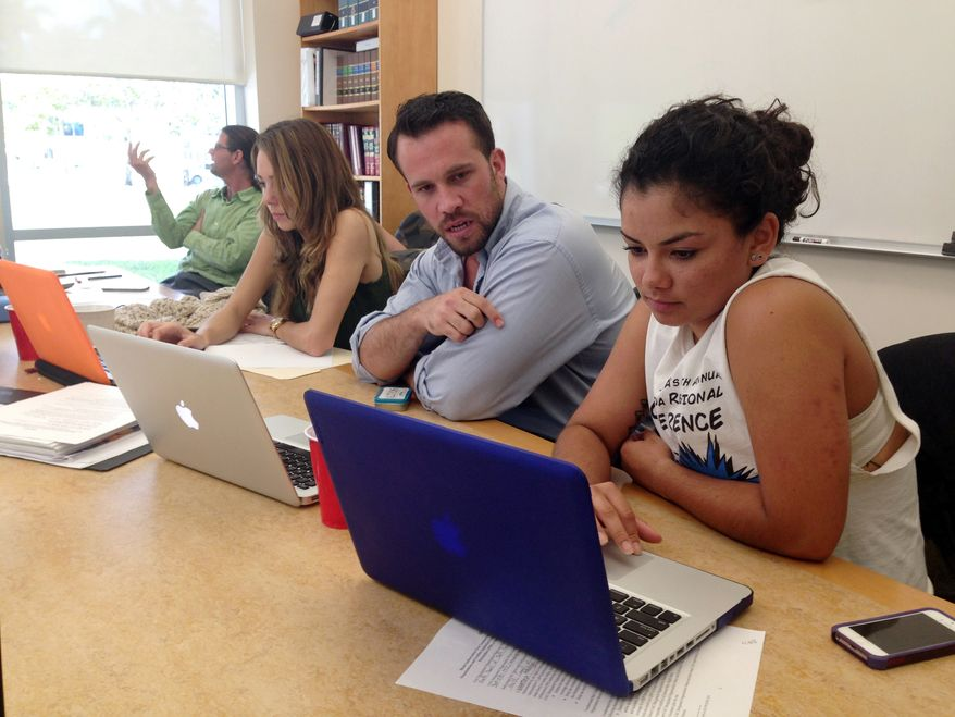 ** FILE ** In this March 21, 2014 file photo, Anthony Rouzier, second right, helps Valentina Adarraga, 20, right, sign up for health insurance under the Affordable Care Act in Miami. (AP Photo/Kelli Kennedy, File)