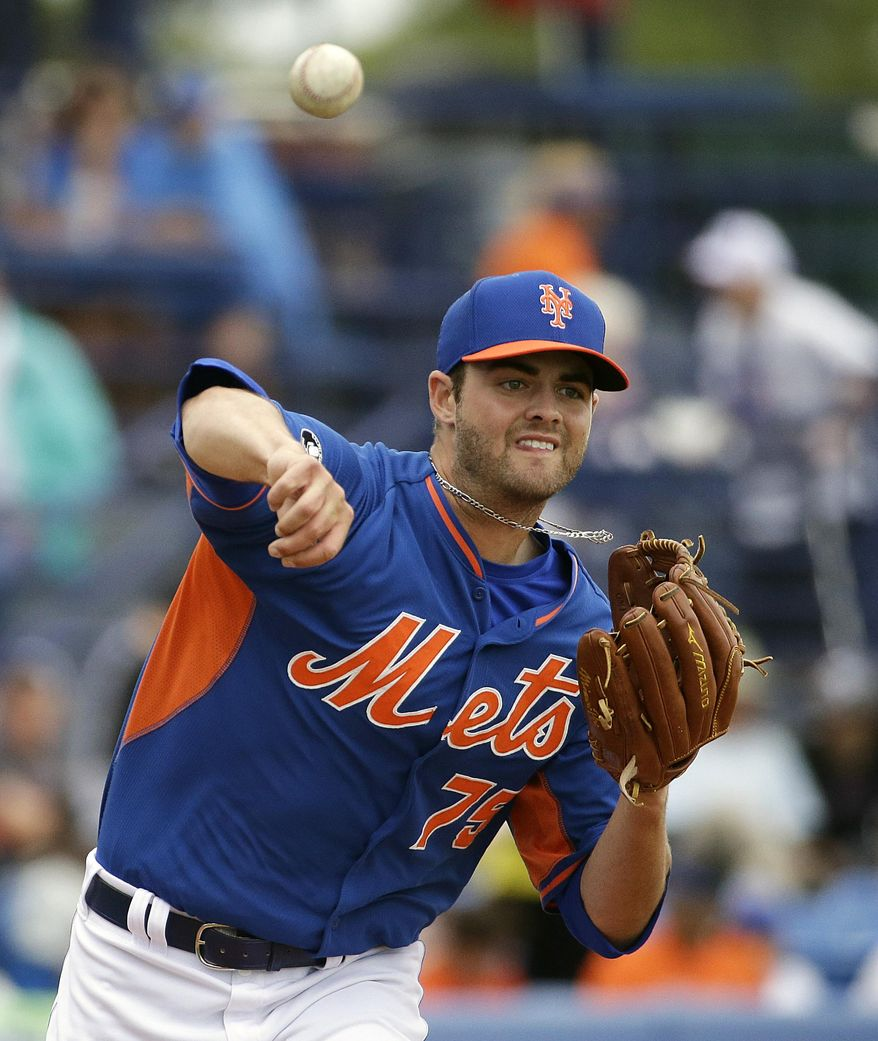 New York Mets starting pitcher Cory Mazzoni throws to first base in pickoff attempt of Washington Nationals' Wilson Ramos in the second inning of an exhibition spring training baseball game, Thursday, March 27, 2014, in Port St. Lucie, Fla. (AP Photo/David Goldman)