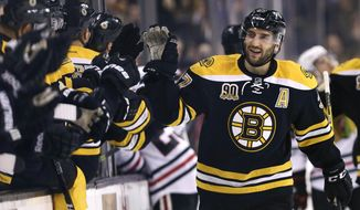 Boston Bruins center Patrice Bergeron, right, is congratulated by teammates after his goal against the Chicago Blackhawks during the first period of an NHL hockey game, Thursday, March 27, 2014, in Boston. (AP Photo/Charles Krupa)