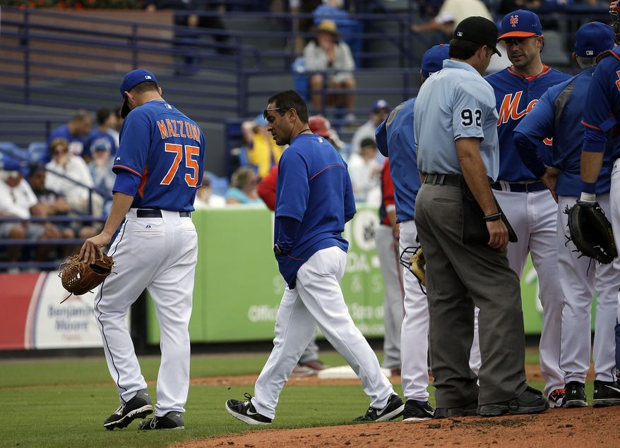 New York Mets starting pitcher Cory Mazzoni, left, leaves the field in the second inning of an exhibition spring training baseball game against the Washington Nationals, Thursday, March 27, 2014, in Port St. Lucie, Fla. (AP Photo/David Goldman)